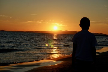 Child on the beach watches the sunset