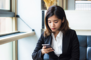 A beautiful Asian business woman executive relaxing in coffee shop holding and using an application in her smart phone to check message, email, or meeting today. Copy space.