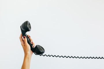 woman's hand holding a vintage telephone  with cord stretched out