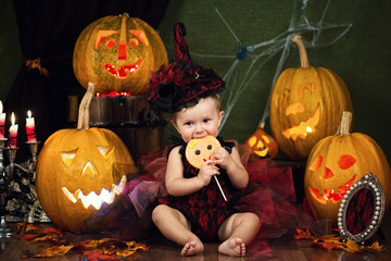 Little witch girl child laughing among pumpkins and candles. Wall mural