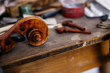 Violin scroll and pegs on a workbench