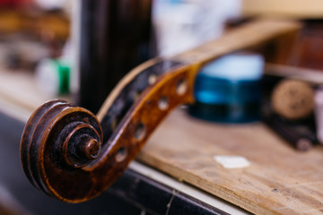 Violin scroll being repaired in a luthier shop
