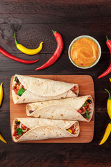 Mexican burritos with cheese salsa, chili peppers, and copyspace