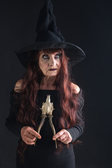 Halloween woman in black with long red hair and makeup.