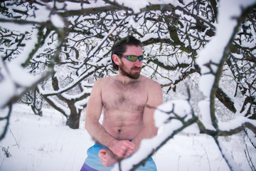 Naked man in sunglasses hiding at winter snowy trees
