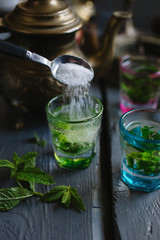 Pouring sugar into mint tea.