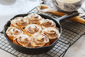 Iced Cinnamon Rolls or Buns Baked in Cast Iron Skillet on Cooling Rack