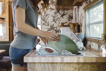 Washing dishes in camper trailer.