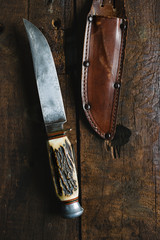 Old hunting knife with leather sheath on wood background.