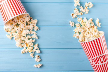 Popcorn horizontal banner. Red stripped paper cup and kernels lying on blue wooden background. Copy space. Top view.