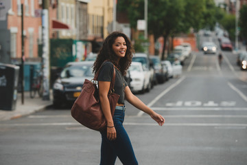 Pretty young woman walking across the street