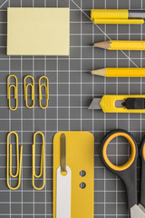 Yellow office utensils on a grey crafting mat