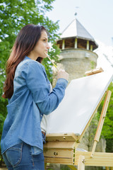 young woman draws on an easel outdoors