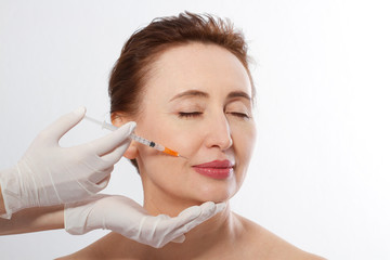 Middle age woman 40s getting lifting botox injection in lips by doctor isolated on white background. Macro. Cosmetic procedures, Botox injections, hyaluronic acid. Copy space and mock up