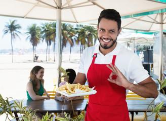 Sympathischer Kellner serviert Pommes Frites