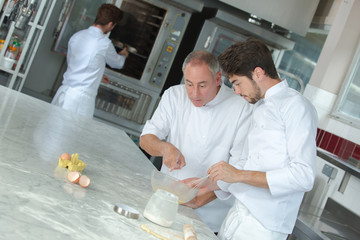 chef and apprentice making pastry