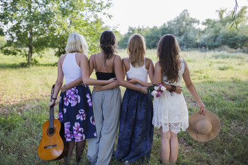 Back view of four happy female friends in nature