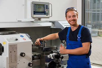 Worker or fitter posing in front of turning machine at workshop
