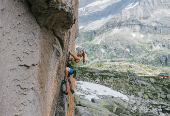 young female rock climber climbing in alpine landscape