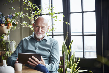 Happy Senior Man Using Digital Tablet At Home