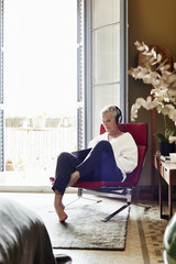 Senior Woman Listening Music While Sitting On Chair At Home