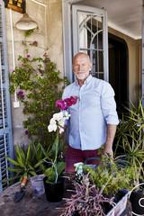 Happy Senior Man Gardening On Balcony