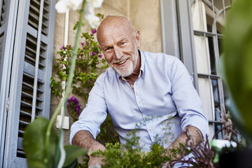 Smiling Senior Man Gardening On Balcony