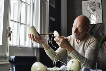 Senior Man Repairing Lamp At Table