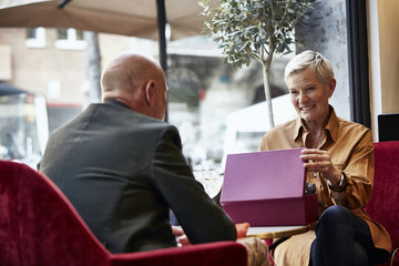 Senior Woman Opening Gift Box While Looking At Man