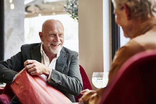 Senior Man Opening Gift While Looking At Woman