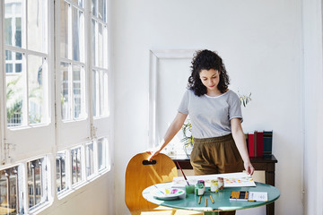 Woman Drawing At Table In House