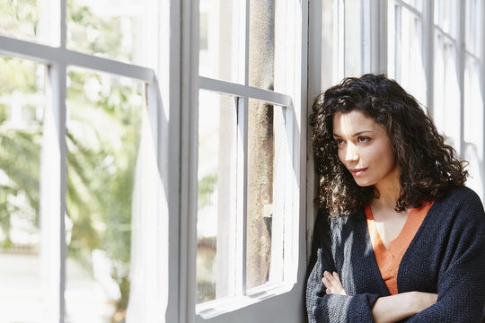 Woman With Coffee Cup Looking Through Window