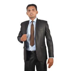 Portrait of a businessman in black suit adjusting coat over white background