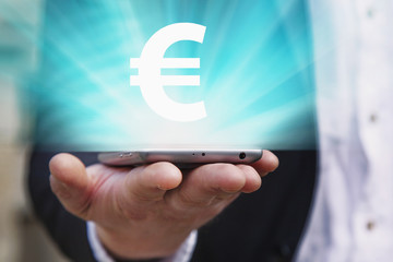 Hand of a businessman shows smart phone with symbol of Euro. Making and transfer of money through mobile banking on the mobile phone.