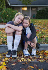 Two Teen Girls Wearing Athletic Clothing Sitting On Curb