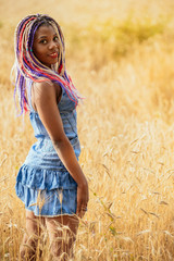 portrait of a beautiful young African American girl with a hair dreddy on the background of wheat, cereals. Concept photo walking outdoors, freedom