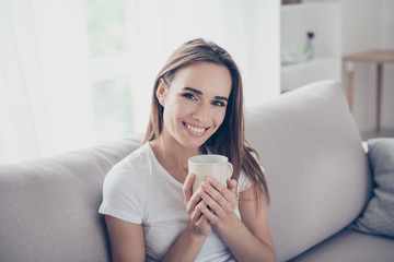 Morning is here! Close up portrait of dreamy gorgeous brown haired freelancer on the beige couch at home having hot beverage, looking in camera, so comfortable, with beaming smile