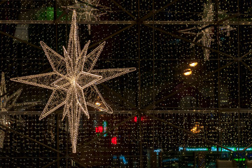 Close-up of piece of large decorative Christmas star on background of bright shop windows. Generous and rich Christmas. Copy space