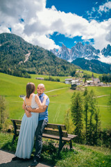 Young couple admires the view in relaxation. Famous best alpine place. Santa Maddalena village with magical Dolomites mountains in background, Val di Funes valley, Trentino Alto Adige Italy