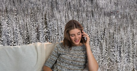 Woman with warm jumper on phone on couch in front of snow forest