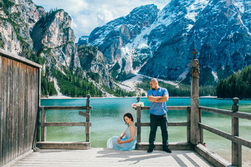Young couple in love on the pier at lake, lago di braies,Dolomite,Italy. Man and woman on vacation in beautiful place.