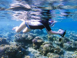 Snorkeling girl with underwater camera in coral reef. Snorkel with camera in underwater housing.