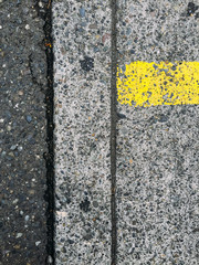 Detail of sidewalk and street curb with yellow strip