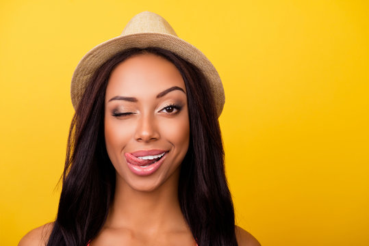 Wow! Healthcare, summer, bodycare, concept. Close up portrait of cheerful coquette afro lady with sticking tongue, looks at camera, wearing beige head wear, so cheerful and carefree