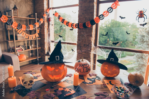 Preparation for halloween, cutted pumpkin, fall leaves, spiders nets, headwear of witch, bowl with candies on top of wooden table. Ready for feast in mystery interior. Concept of all hallows eve