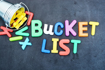 Bucket list concept, things to do in life with iron bucket and magnetic letters on chalkboard