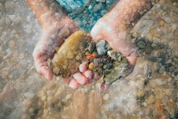 Hands holding rocks, close-up, double exposure