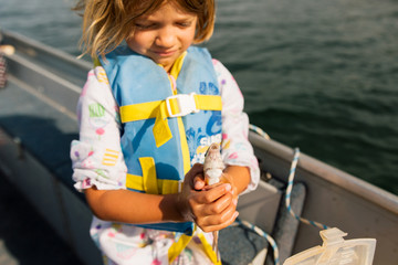 Girl holding fish on boat
