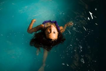 Girl swimming in swimming pool, overhead view