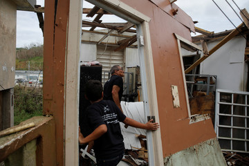 Juan Rodriguez and Ian Rodriguez Rivera look at the home of a relative damaged by Hurricane Maria near the municipality of Orocovis, outside San Juan